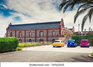 Adelaide, Australia - January 16, 2016: Vintage colourful cars parked near Chateau Tanunda winery on a bright day, viewed from main entrance.