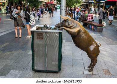 Adelaide, Australia - March 16, 2017.  Street view on Rundle Mall pedestrian street in Adelaide, SA, with sculpture of life-size bronze pig, known as Oliver, rooting around a rubbish bin, and people.