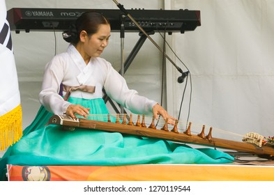 Adelaide, Australia - November 11 2017: A female musician dressed in a hanbok plays a  gayageum at the Korean Culture and Food Festival.