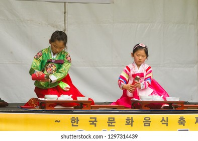 Adelaide, Australia - November 11 2017: Two young children participate in a traditional tea ceremony at the Korean Culture and Food Festival.