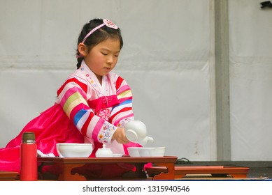 Adelaide, Australia - November 11 2017: A young girl pours tea as part of a traditional tea ceremony at the Korean Culture and Food Festival.