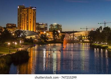 Adelaide, Australia - November, 2016: Adelaide city CBD at sunrise view across Torrens river from park footbridge.