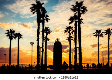 Adelaide, Australia - October 7, 2017: Walking people and Pioneer Memorial silhouettes at Moseley Square on Glenelg during sunset.