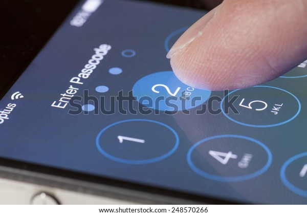Adelaide, Australia - September 20, 2013: Entering passcode on an iPhone running iOS. iOS is the foundation of iPhone, iPad, and iPod touch. It comes with a collection of apps and useful features.
