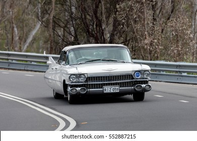 Adelaide, Australia - September 25, 2016: Vintage 1959 Cadillac DeVille Convertible driving on country roads near the town of Birdwood, South Australia.
