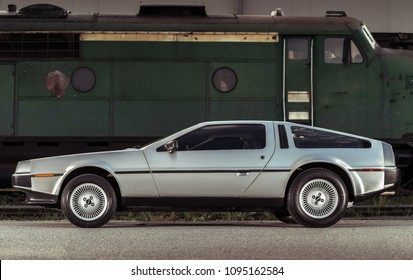 Adelaide, Australia - September 7, 2013: Legendary DeLorean DMC-12 stainless steel car parked next to train on street