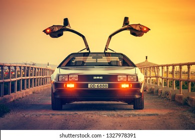 Adelaide, Australia - September 7, 2013: DeLorean DMC-12 car front view with opened gull-wing doors parked on the bridge at dusk