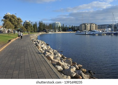 ADELAIDE - MAY 06 2019:People walking on footpath along Glenelg Marina, a popular tourist attraction in in Glenelg Adelaide South Australia