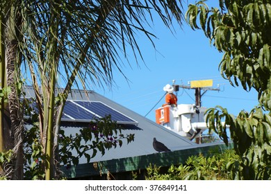 ADELAIDE, SOUTH AUSTRALIA - FEBRUARY 12, 2016: View of electricity power line repair and service worker next to home with solar panels from suburban garden.