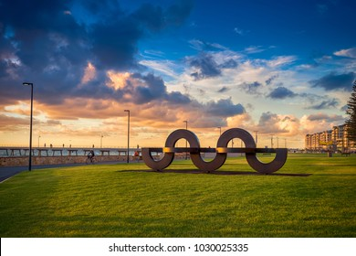 Adelaide, South Australia - February 25, 2016: Wave shaped installation in Jimmy Melrose Park at Glenelg viewed towards jetty at sunset