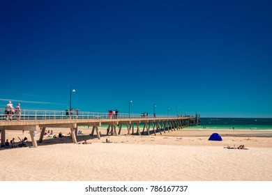 Adelaide, South Australia - February 28, 2016: People walking along Glenelg beach jetty on a bright summer day viewed from Moseley Square