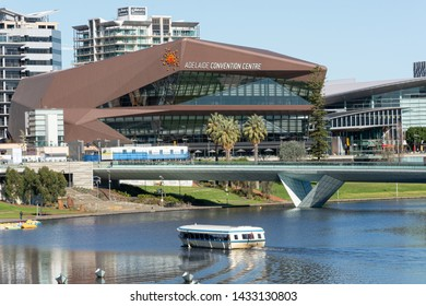 Adelaide, South Australia / Australia - June  22 2019: Adelaide Convention Centre and River Torrens Footbridge with Popeye river cruiser in forground. River Torrens, Adelaide Riverbank Precinct.