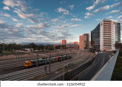 Adelaide, South Australia / Australia - June 24 2018: Train leaves the station in Adelaide city with University of Adelaide building visible in the background
