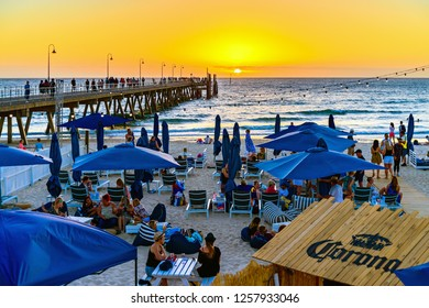 Adelaide, South Australia - March 11, 2018: People at The Moseley Beach Club cafe enjoying sunset view on a summer evening