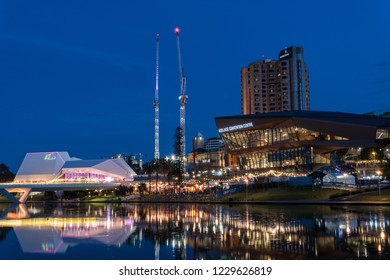 Adelaide, South Australia - October 31, 2018: cranes and construction on the banks of the torrens river in Adelaide city after sunset at blue hour.