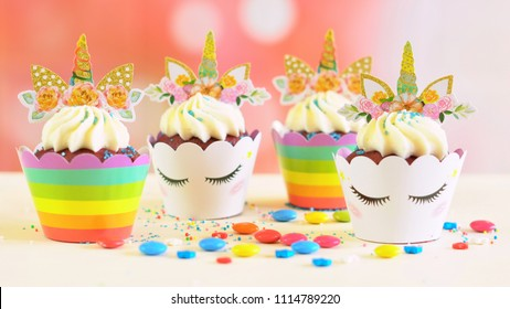 Adelaide, South Adelaide - June 15, 2018: Children's birthday party unicorn and rainbow themed cupcakes, close up against a colorful pastel background.