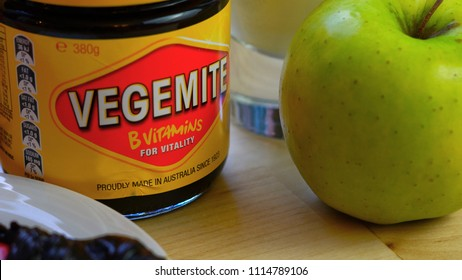 Adelaide, South Adelaide - June 6, 2018: Australian Vegemite spread in iconic red and yellow jar served with glass of milk and green apple.
