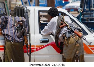 ADEN, YEMEN - SEPTEMBER 14, 2006: Unidentified Yemeni men with Kalashnikov machine guns talk to a car driver in Aden, Yemen.