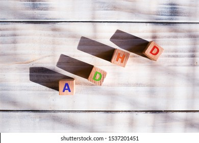 ADHD abbreviation letters on wooden cubes, white background. Mental health issues