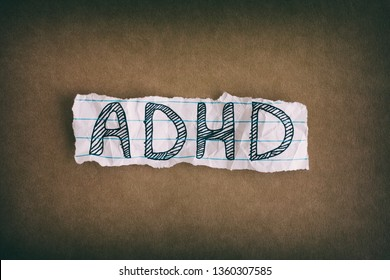 ADHD. Abbreviation ADHD on brown background. Close up. ADHD is Attention deficit hyperactivity disorder.