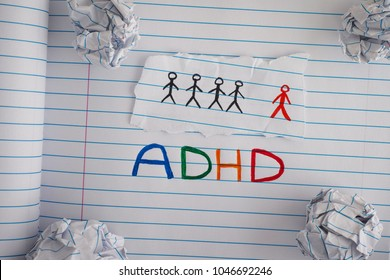 ADHD. Abbreviation ADHD on notebook sheet with some crumpled paper balls on it. Close up. ADHD is Attention deficit hyperactivity disorder.