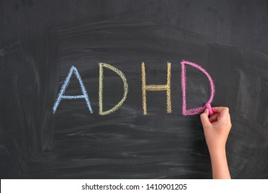 ADHD. Child writing Abbreviation ADHD on a blackboard. ADHD is Attention deficit hyperactivity disorder.