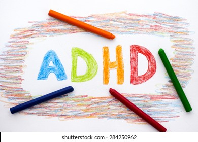 ADHD written on sheet of paper by crayons. ADHD is Attention deficit hyperactivity disorder.