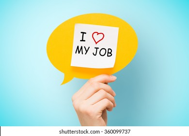 """Adhesive note on yellow speech bubble with """"I love my job"""" words on blue background."""