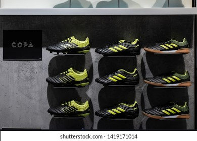 Adidas Copa soccer shoes: firm ground cleats, indoor sala shoes and turf shoes in core black and solar yellow colorway on Adidas store display. Krasnoyarsk, Russia - June 3, 2019