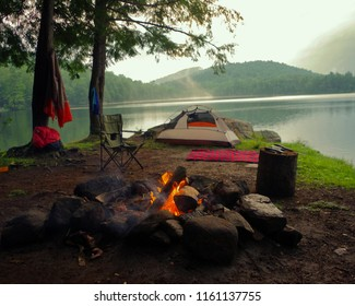 Adirondack Campsite with Campfire, tent shelter on a mountain lake in the summer. Summertime camping in Upstate New York.