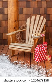 Adirondack chair with Christmas gifts and cookies snacks on the snowy wooden porch deck of a rustic country cabin. Winter holiday vacation home.