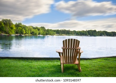 Adirondack chair on a green grass carpet facing a calm lake. Across the water are cottages nestled among green trees.