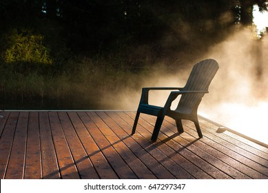 Adirondack chair on wooden dock illuminated by the morning sun and fog.