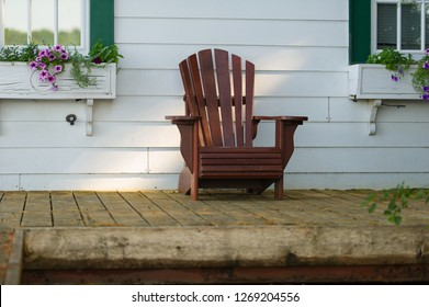 Adirondack chair sit on a cottage porch. The cottage is white and some flower pots are visible. The porch is wooden made.