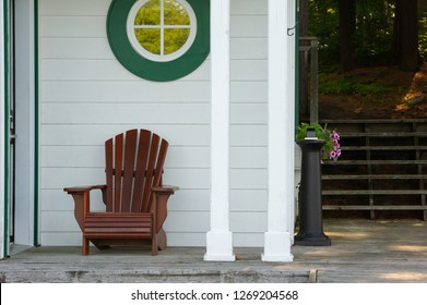 Adirondack chair sit on a cottage porch near the entrance. The building is white and a round window is visible. In the background there are some pink flowers.