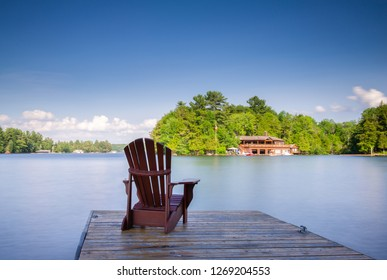 Adirondack chair sit on a wooden dock facing a calm waters of a lake. In the background there's a brown cottage nestled between trees.