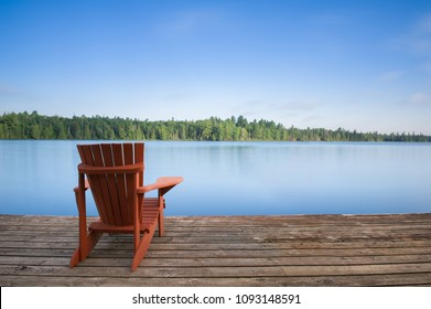 Adirondack chair sitting on a wood dock facing a calm lake. Across the water there are green trees.