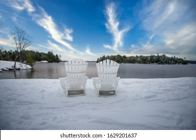Adirondack chairs covered in snow facing a lake in Muskoka, Ontario Canada. The sky is blue with some cloud formations