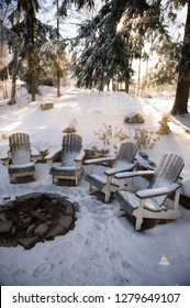 Adirondack chairs near a fire pit covered in snow at a cottage in Muskoka, Ontario Canada. The sun rays are breaking through between the tree branches.