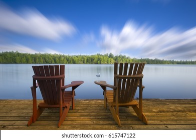 Adirondack chairs on a lake deck Two Adirondack chairs sitting on a wood dock facing a lake. The wood on the dock is arranged in an horizontal pattern. On one of the chairs there's a glass of wine.