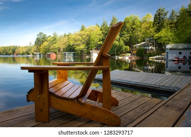 Adirondack chairs on a wooden dock facing the blue waters of a calm lake in  Muskoka, Ontario Canada. Cottages nestled between trees are visible in the background.
