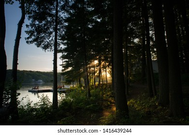 Adirondack chairs on a wooden dock facing a calm lake during a summer sunrise. Across the blue waters, there are cottages nestled between green trees. Sunbeams are filtering through the woods.