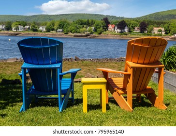 Adirondack chairs overlooking a river.