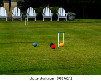 Adirondack chairs sit behind a croquet court where multiple balls are being played around a hoop or wicket on a relaxing summer day.