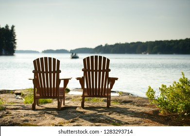 Adirondack chairs sit on a rock formation facing the waters of a lake during a sunny summer day in Muskoka, Ontario Canada. In the background a water boat is visible.