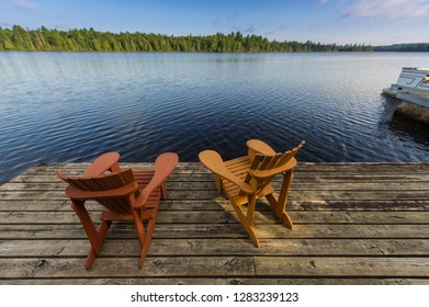 Adirondack chairs sit on a wooden dock facing the blue water of a lake. Portion of a boat is visible.