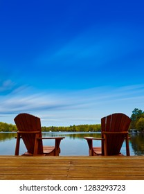 Adirondack chairs sit on a wooden dock facing the waters of a lake during a sunny summer day in Muskoka, Ontario Canada. Cottages are visible nestled between trees in the background.