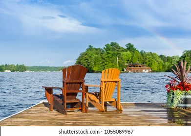 Adirondack chairs sitting on a wood dock facing a lake. Across the water is a brown cottage nestled among green trees.