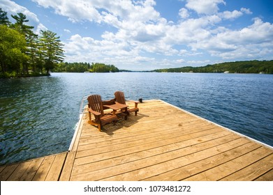 Adirondack chairs sitting on a wood dock facing a lake