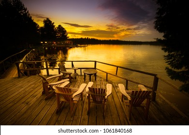 Adirondack chairs sitting on a wooden dock facing a lake at sunset.